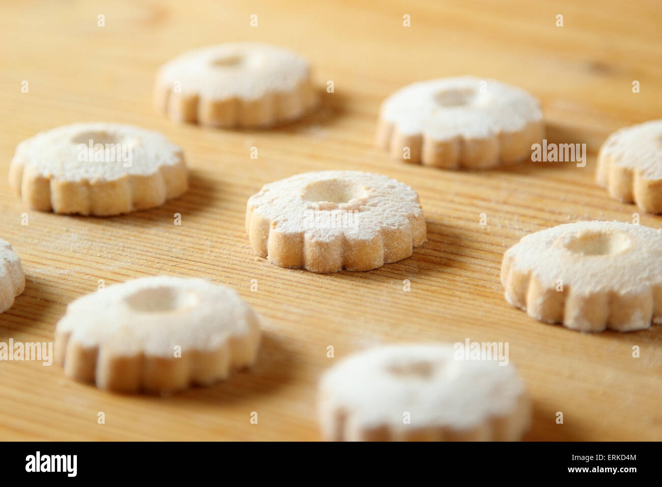 Regular arrangement of italian canestrelli biscuits on a wooden table with powdered sugar on the surface - Stock Image