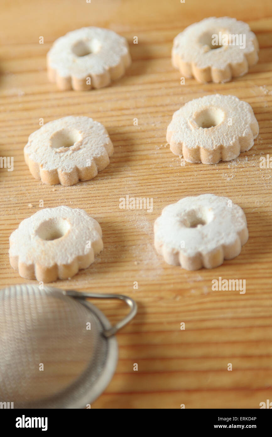 Regular arrangement of italian canestrelli biscuits on a wooden table with a strainer used to sprinkle powdered - Stock Image