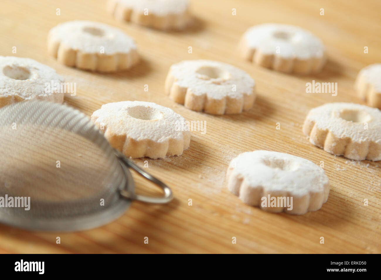 Regular arrangement of italian canestrelli cookies on a raw wooden table with a strainer used to sprinkle icing - Stock Image