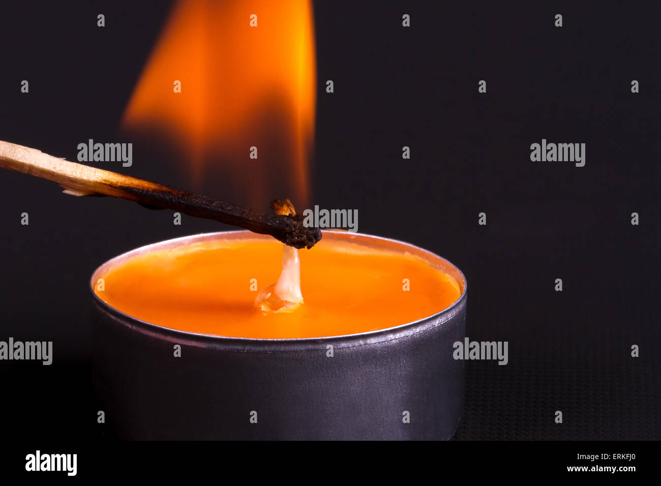 Close up detailed front view of orange candle, burning with a match, on black background. - Stock Image