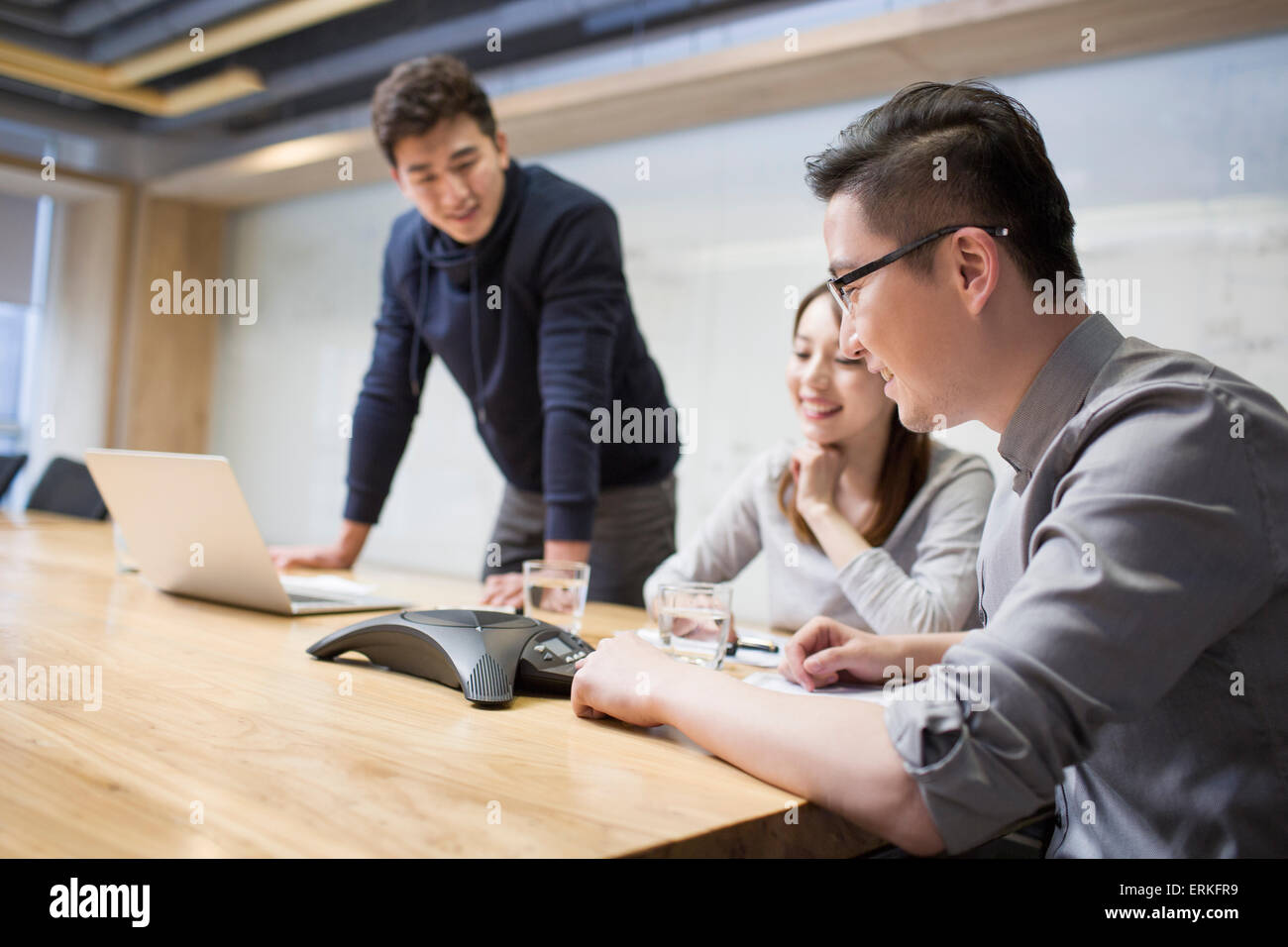 Business people having teleconference in board room - Stock Image
