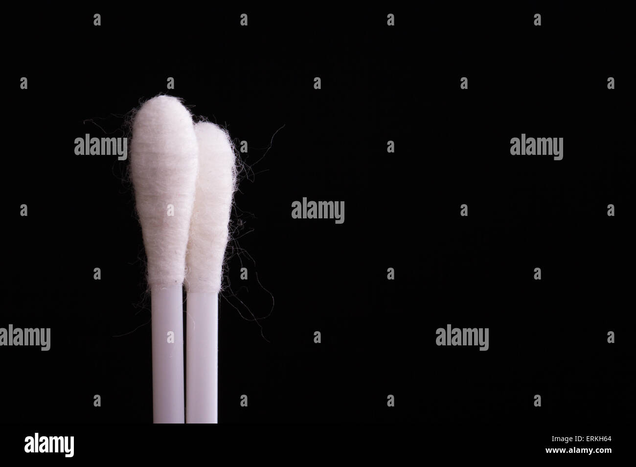 White cotton swabs on black background. - Stock Image