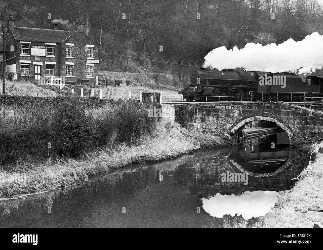 A goods train chuffing past the Black Lion at Consall Forge near Leek,  February 1965. - Stock Image