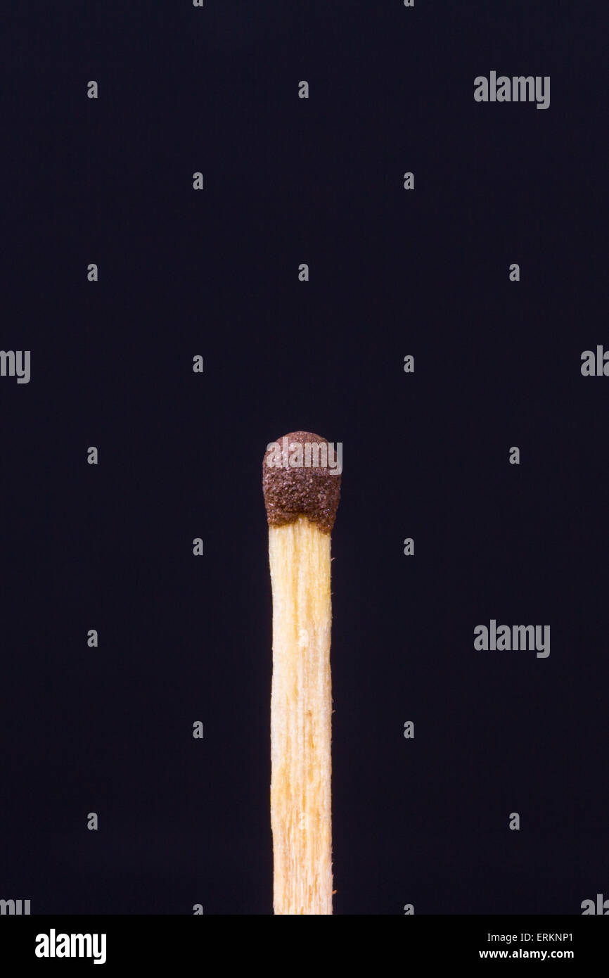 Close up detailed front view of a match, on black background. - Stock Image