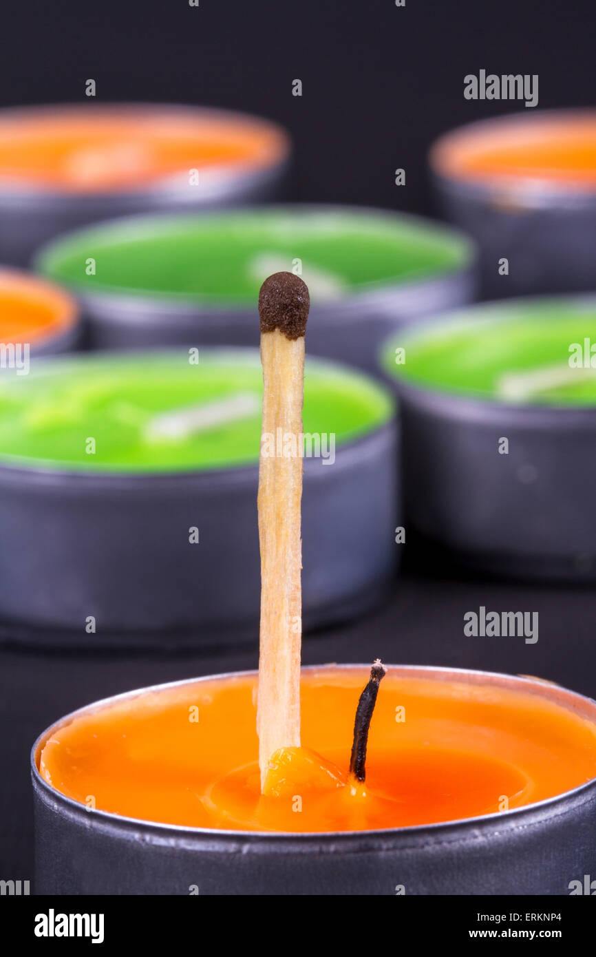 Close up detailed front view of a match, in front of candles, on black background. - Stock Image