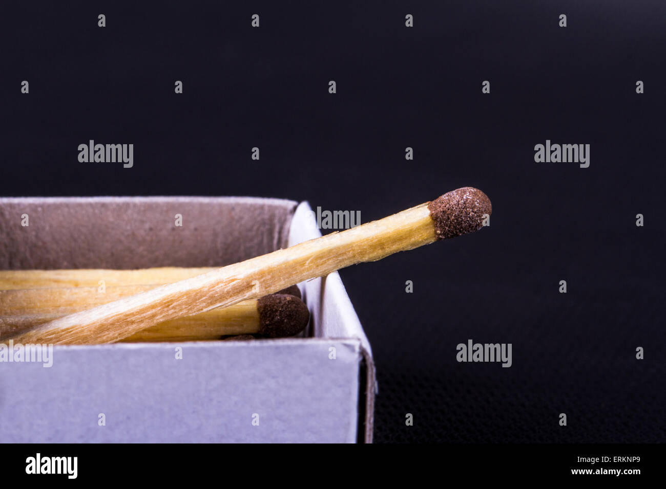 Close up detailed front view of a match in a matchbox, on black background. - Stock Image