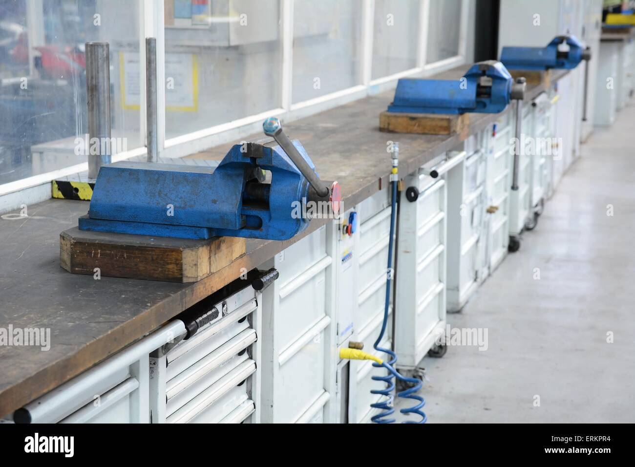 Vice clamps on the bench in the factory hall. - Stock Image