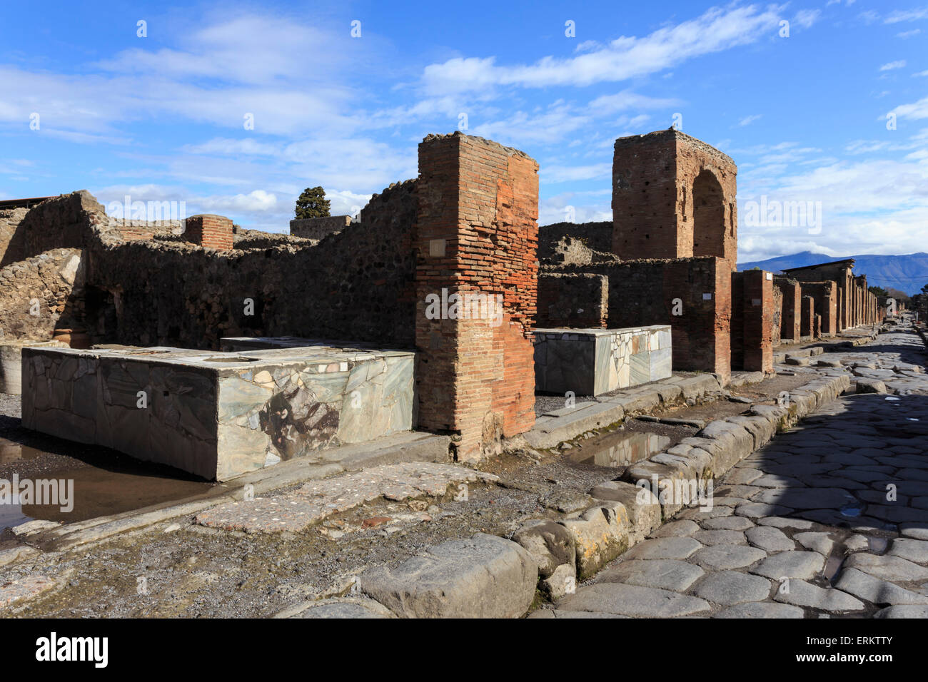 Cobbled street with thermopolium counters and arch, Roman ruins of Pompeii, UNESCO World Heritage Site, Campania, - Stock Image