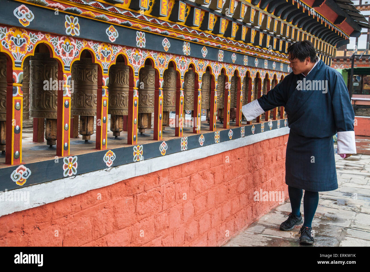 A man rotates the roller-books of the Monastery of Rinpung Dzong which are used to pray, Paro, Bhutan, Asia - Stock Image
