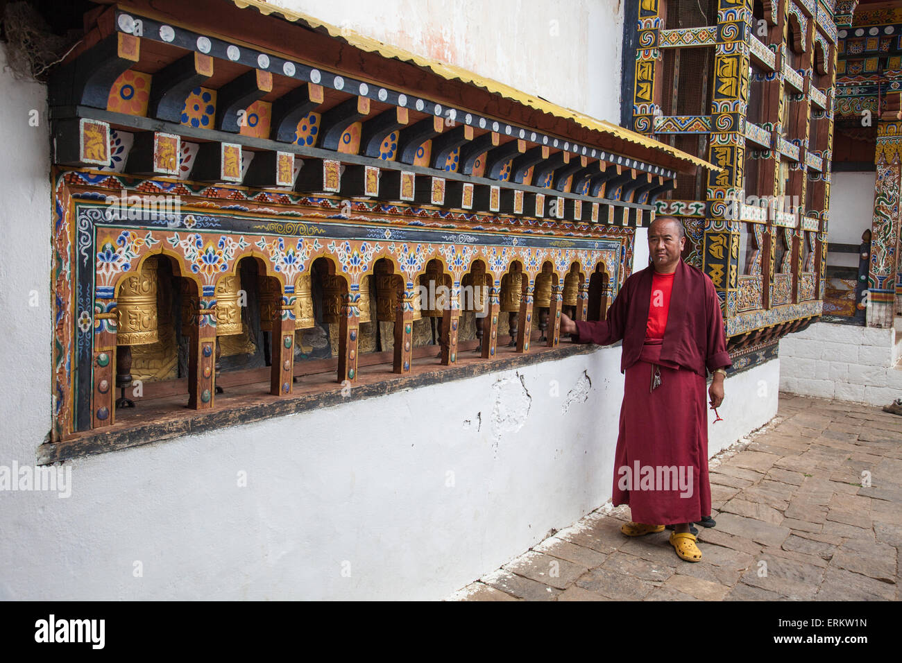 A monk rotates the roller-books of the Monastery of Punakha Dzong which are used to pray, Paro, Bhutan, Asia - Stock Image