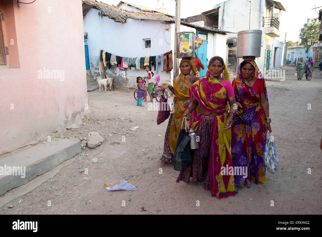 Three women in colourful saris, returning from the well with oil can and pots full of water, Dasada, Gujarat, India - Stock Image