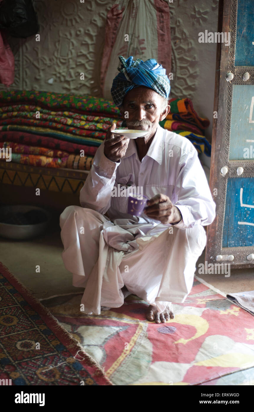Turbanned man sipping tea from saucer in tribal home, Soyla, Kachchh, Gujarat, India - Stock Image