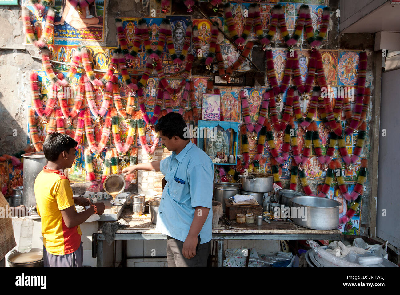 Chai wallah pouring chai (tea) at chai stall decorated with religious posters and malas (garlands), Ahmedabad, Gujarat, - Stock Image