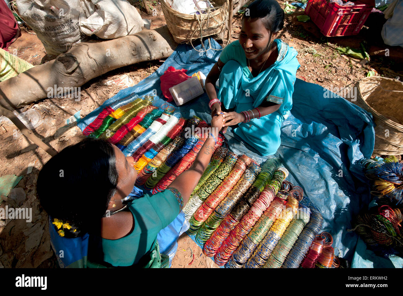 Young woman in turquoise sari selling bangles in Mali weekly tribal market, Guneipada, Koraput district, Orissa - Stock Image