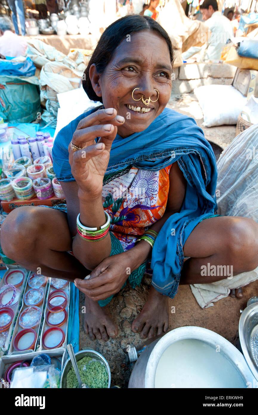Smiling Mali tribeswoman with gold noserings selling yoghourt in Mali weekly tribal market, Guneipada, Orissa (Odisha), - Stock Image