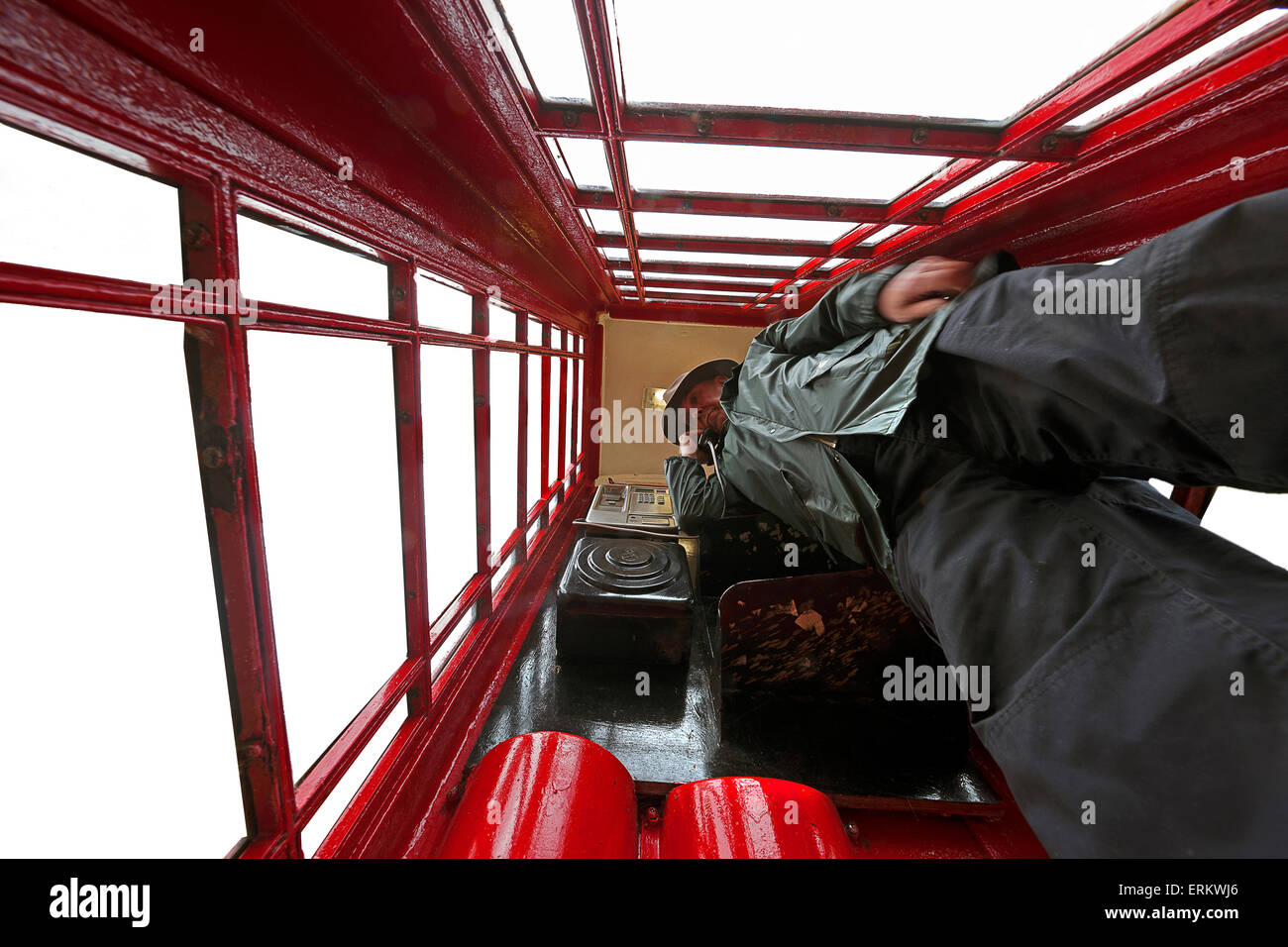 Man inside red  telephone box. - Stock Image