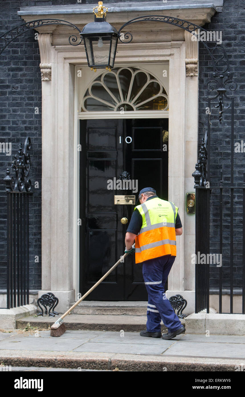 Roadsweeper sweeping the door of Number 10 Downing Street - Stock Image