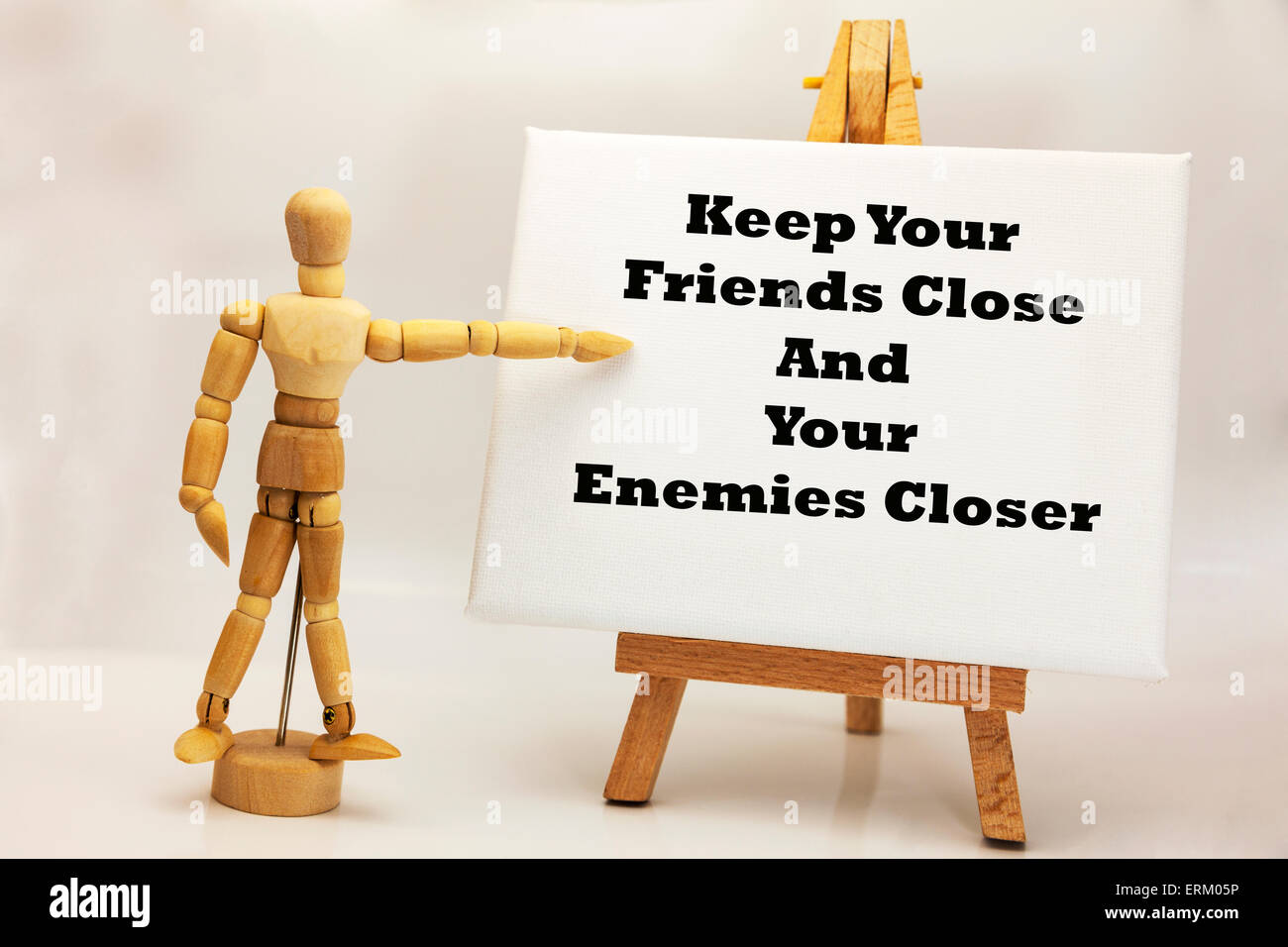 Wooden man with white board pointing at words 'keep your friends close and your enemies closer' business - Stock Image