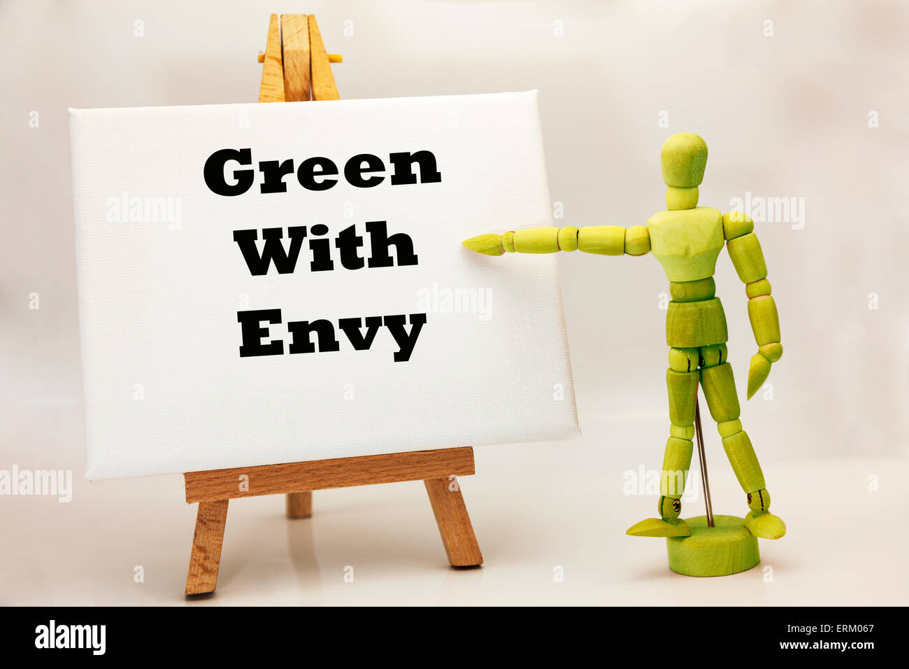 """Wooden man with white board pointing at words """"Green with envy"""" jealous jealousy envious wanting wants Stock Photo"""