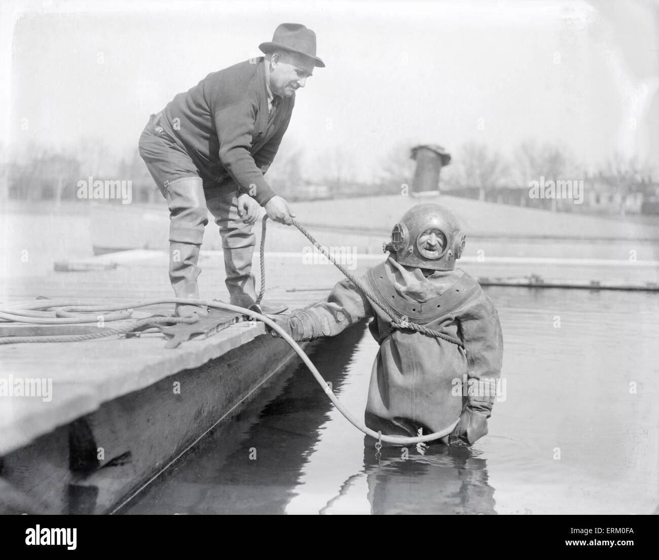 Antique 1929 photograph, diver John Robinson in Standard diving dress at Harvard's Newell Boat House on the - Stock Image