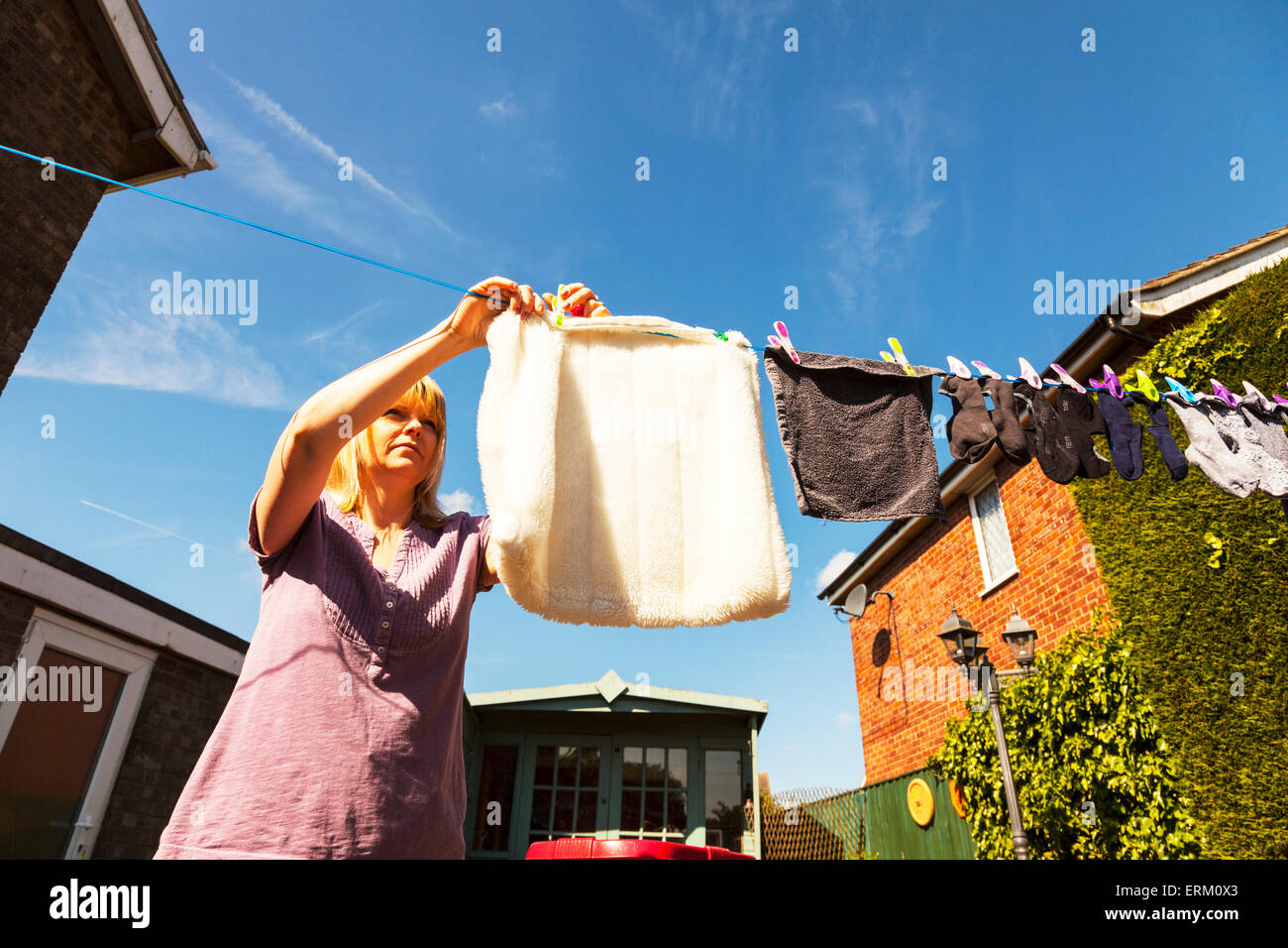 hanging out the washing to dry woman lady female smalls socks line pegging pegs laundry chore womans work never - Stock Image
