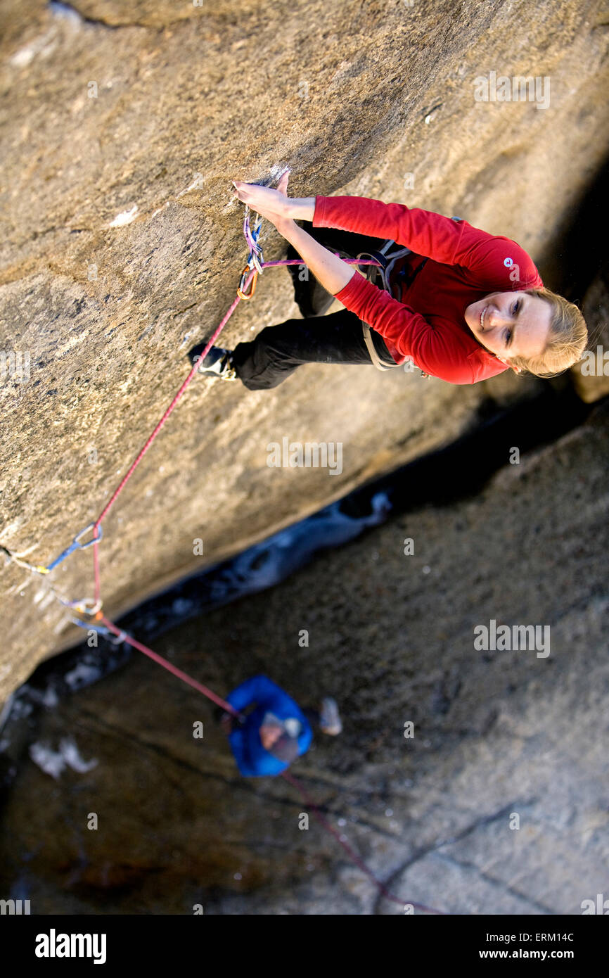Woman climbing a small crack above her belay partner and a river in Yosemite National Park, California. - Stock Image
