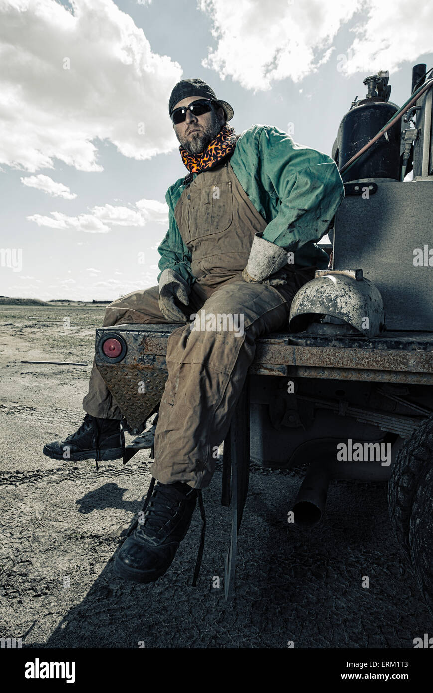 A welder seated on a truck with his gear beside him. - Stock Image