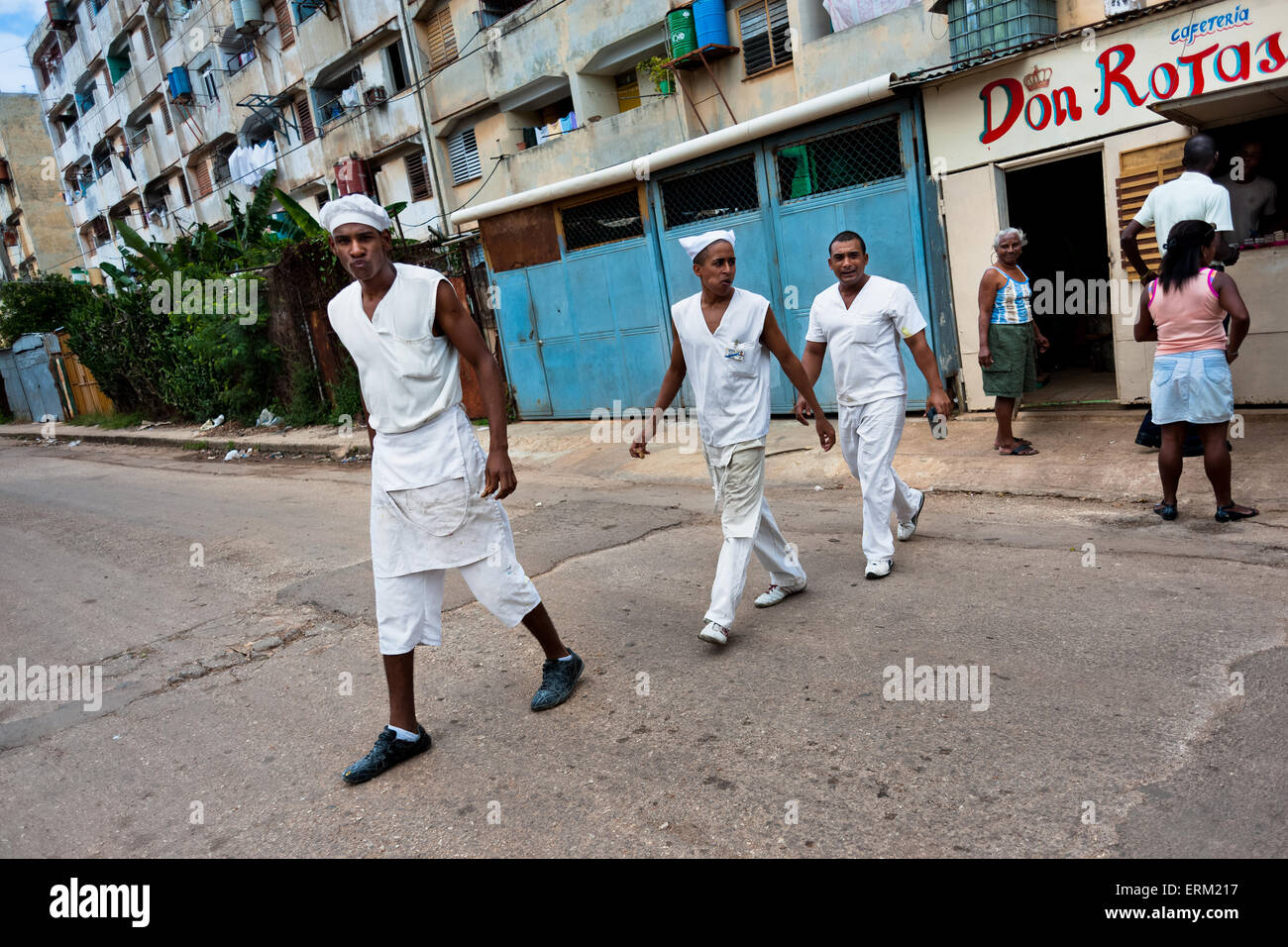 Cuban cooks walk out of the cafeteria in the apartment block in Alamar, a public housing periphery of Havana, Cuba. - Stock Image