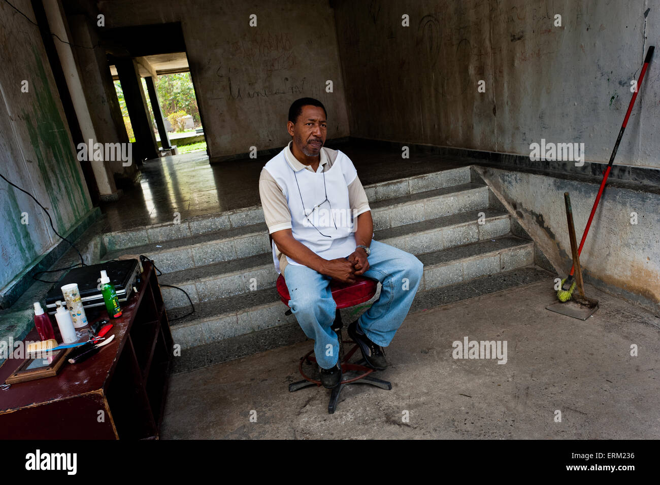 A Cuban barber, waiting for customers, sits in the entrance to the apartment block in a public housing suburb of - Stock Image