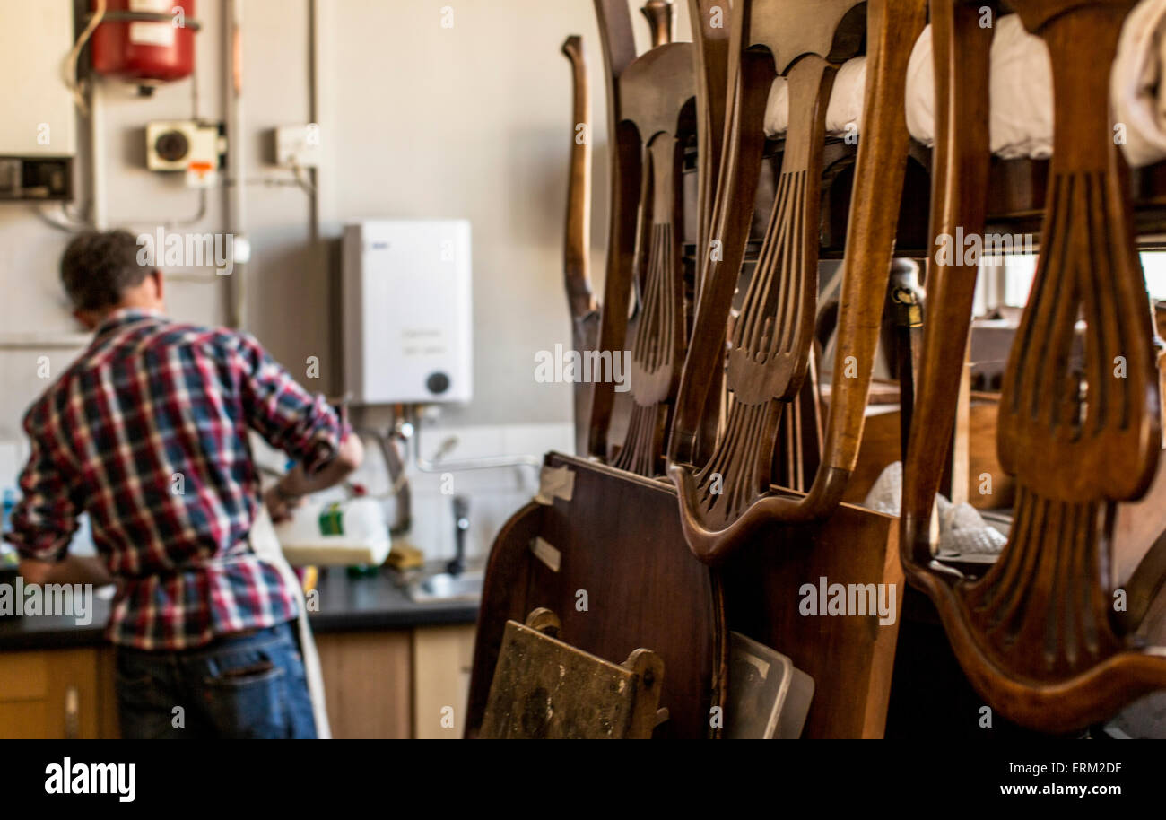 An antique furniture restorer's workshop, chairs piled on a workbench. - Stock Image