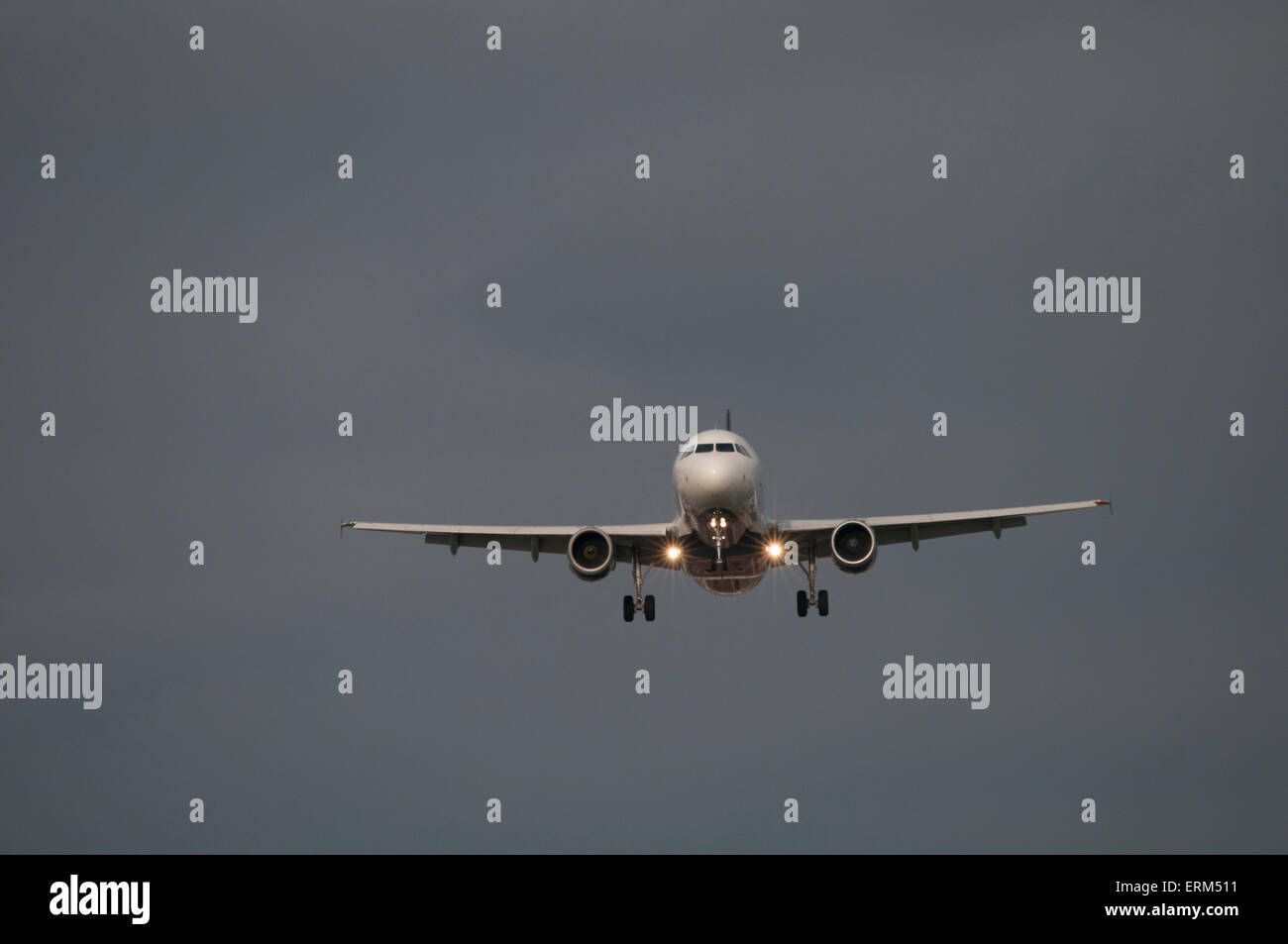 Commercial airliner on final approach - head-on view. - Stock Image