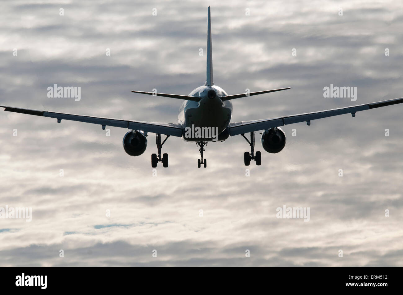 Commercial jet on final approach, in partial silhouette with backdrop of scattered cloud - Stock Image