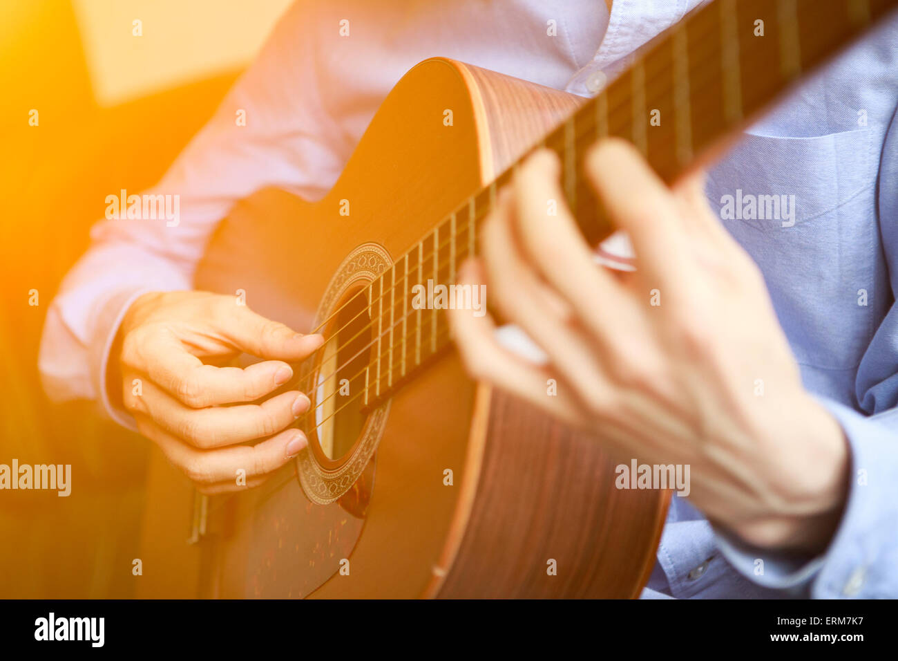 Young musician playing at acoustic guitar - Stock Image