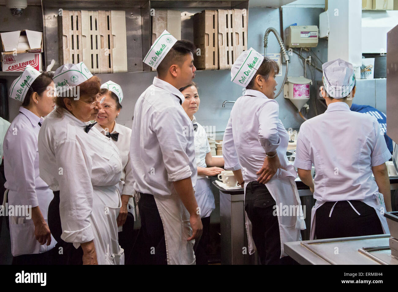 New Orleans, Louisiana - Servers at Café du Monde in the French Market wait in the kitchen to pick up orders - Stock Image