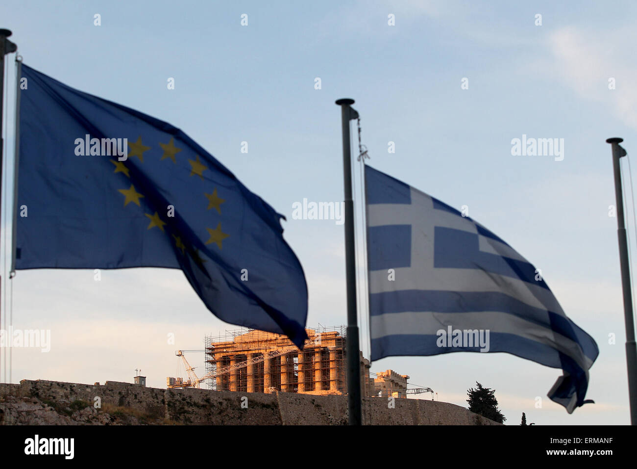 Athens, Greece. 4th June, 2015. Greek and European Union flags fly while the sun sets over the Acropolis, in Athens, - Stock Image
