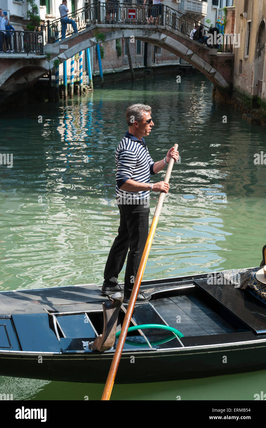 VENICE, ITALY - APRIL 24, 2013: Venetian gondolier punts his gondola along the green waters of a canal. - Stock Image