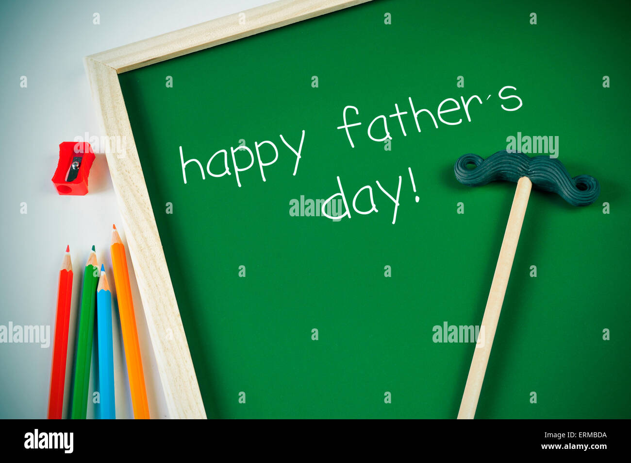 some colored pencils of different colors and a framed green chalkboard with the text happy fathers day written in - Stock Image