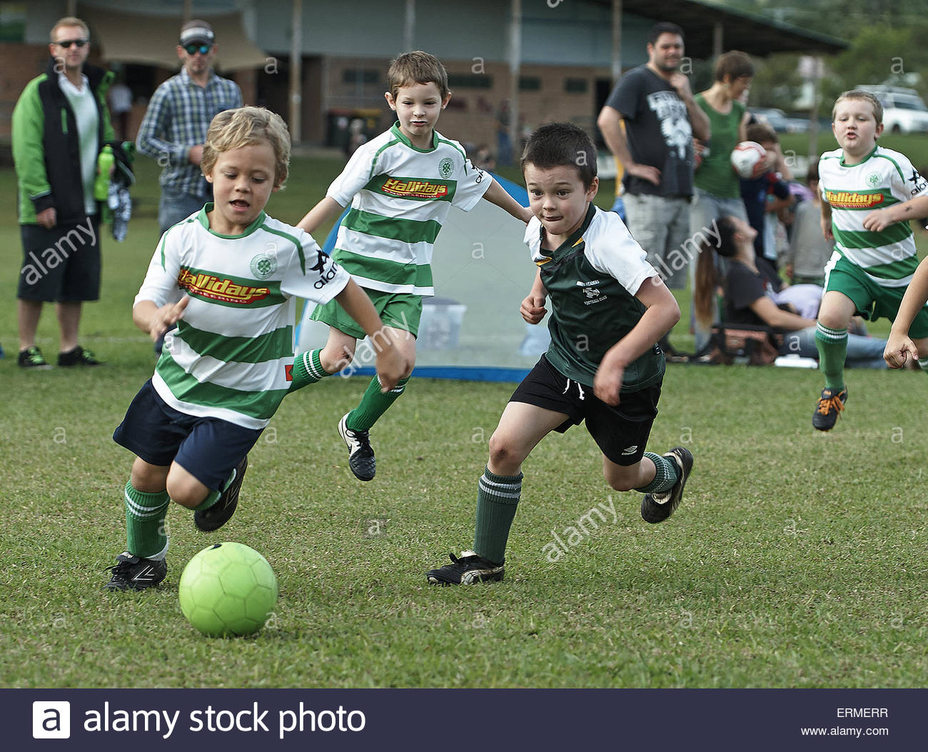 young boys striving to gain possession of the ball during a weekend football match in Nimbin, NSW, Australia. - Stock Image