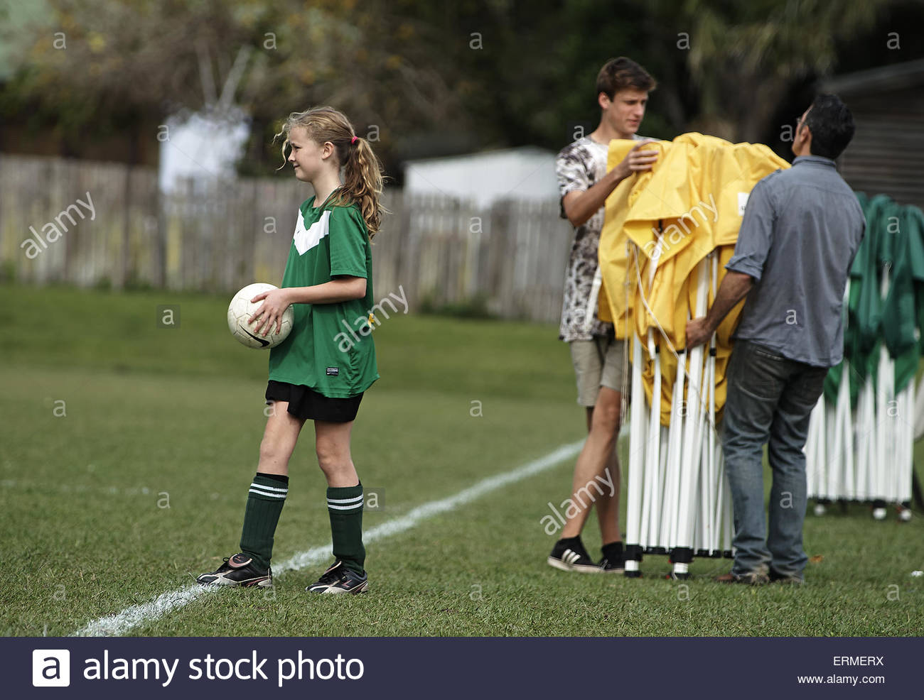 a girl prepares to take a throw in from the sideline, during a weekend football match at the Nimbin Headers soccer - Stock Image