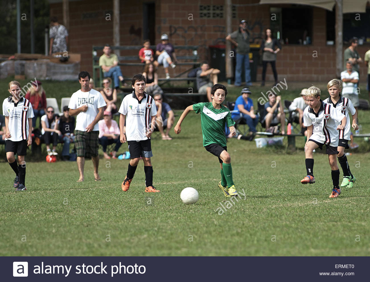 young junior soccer boy player dribbling the ball ahead of the opposition team - Stock Image
