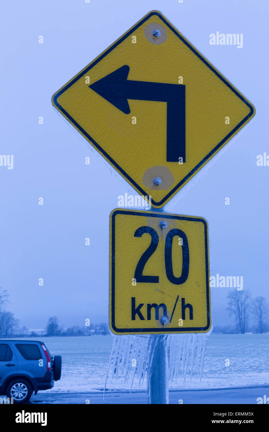 Road sign indicating speed at left turn with icicles hanging from it; British Columbia, Canada Stock Photo