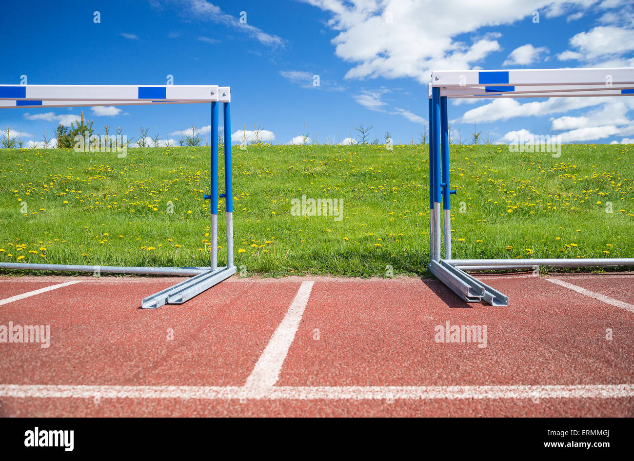 Hurdles stacked at the edge of athletics race track on a sunny summer day - Stock Image