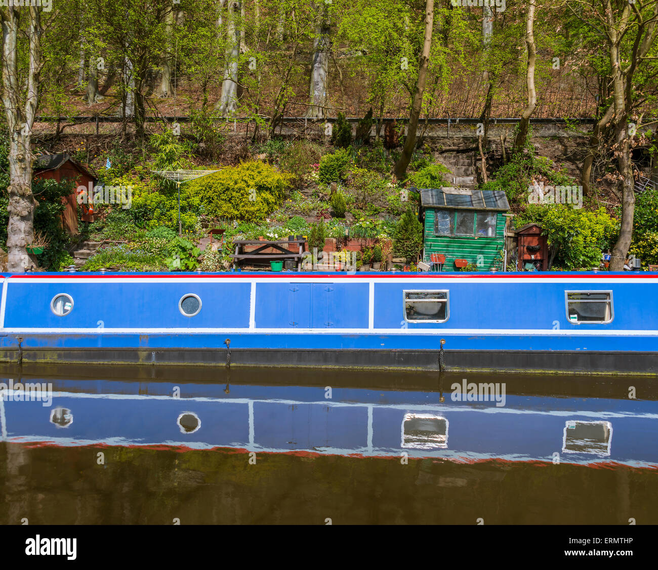 A narrowboat moored alongside some untidy garden items - Stock Image