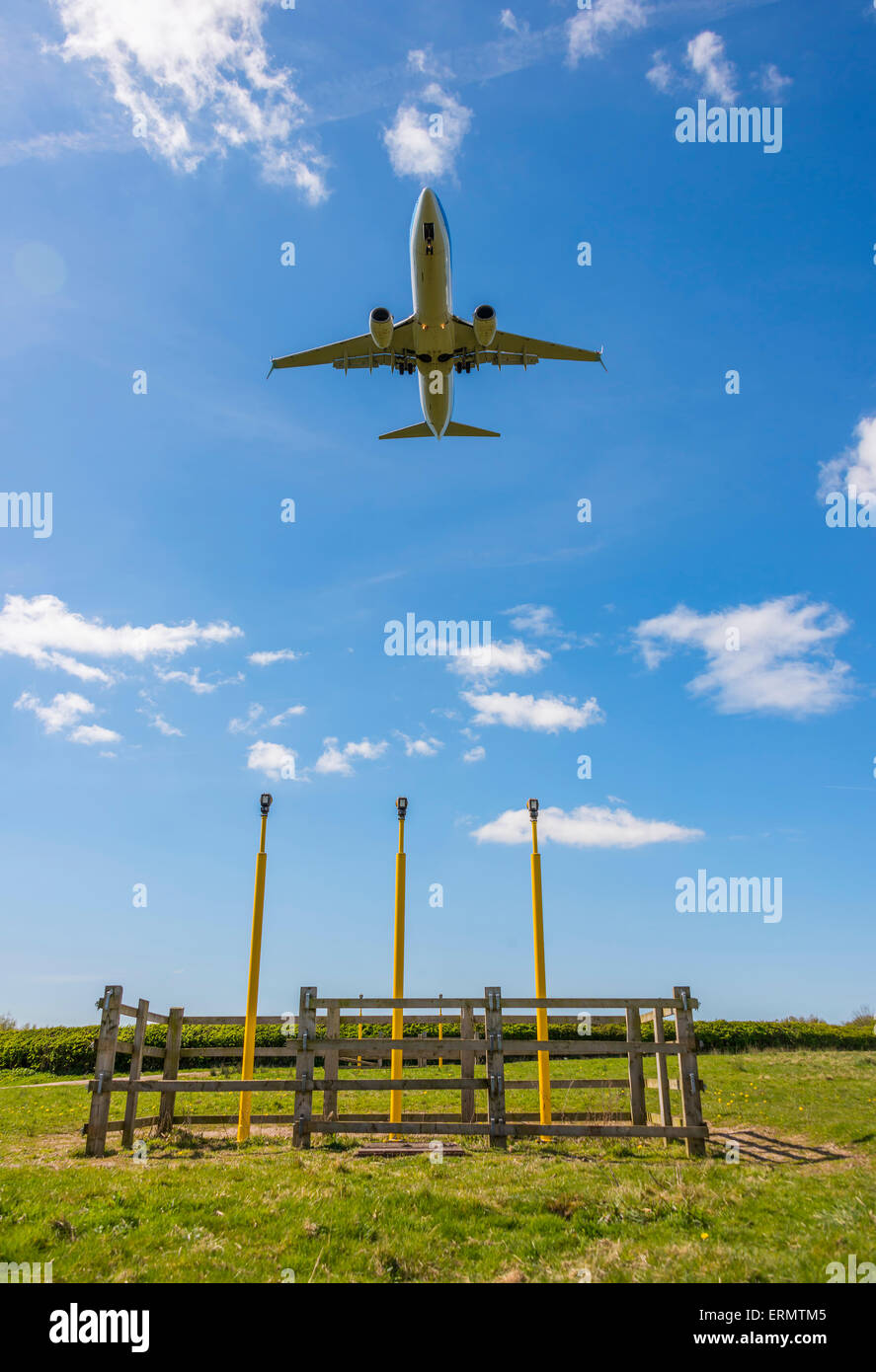 aircraft approaching Manchester over the field containing the runway approach lights - Stock Image