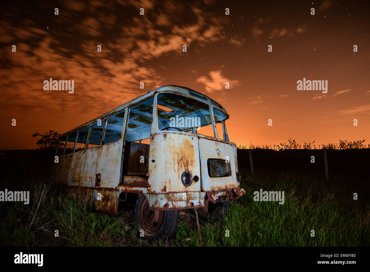 Old rusty bus in unusual  light at night sky and stars background - Stock Image