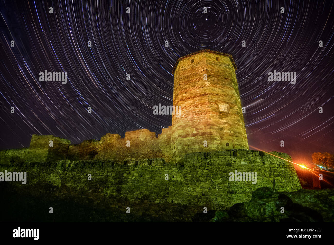 Old stone tower on starry night skyes background   lighthouse - Stock Image