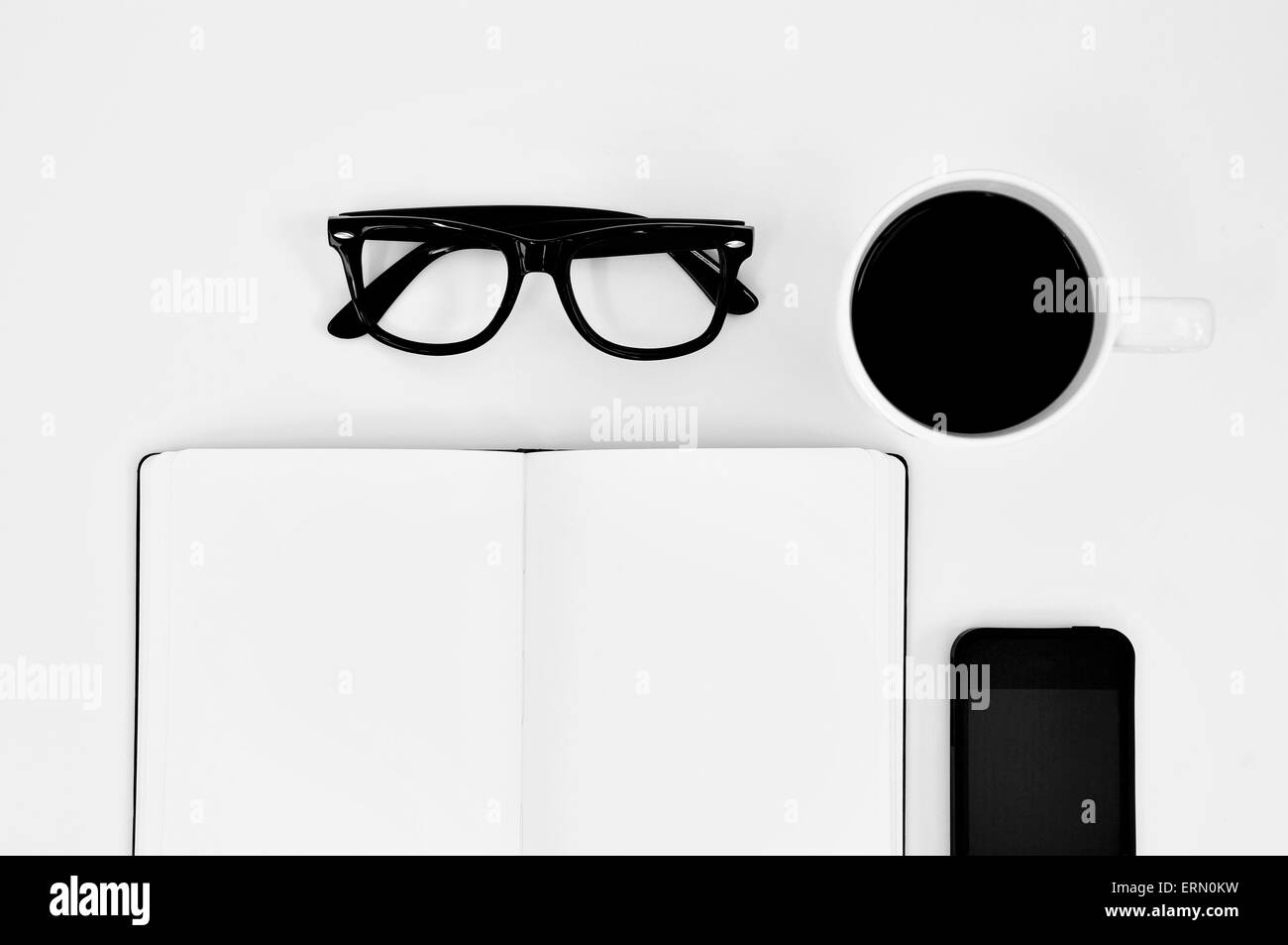 high-angle shot of a blank notebook, a pair of black plastic-rimmed eyeglasses, a cup of coffee and a smartphone - Stock Image