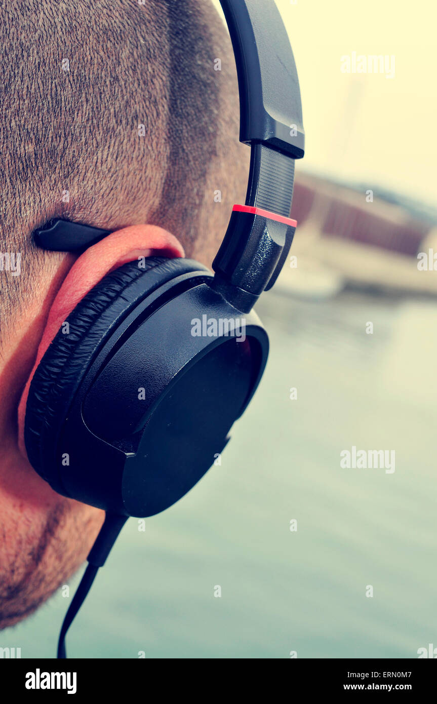 closeup of a young caucasian man listening to music with headphones in front of the sea - Stock Image