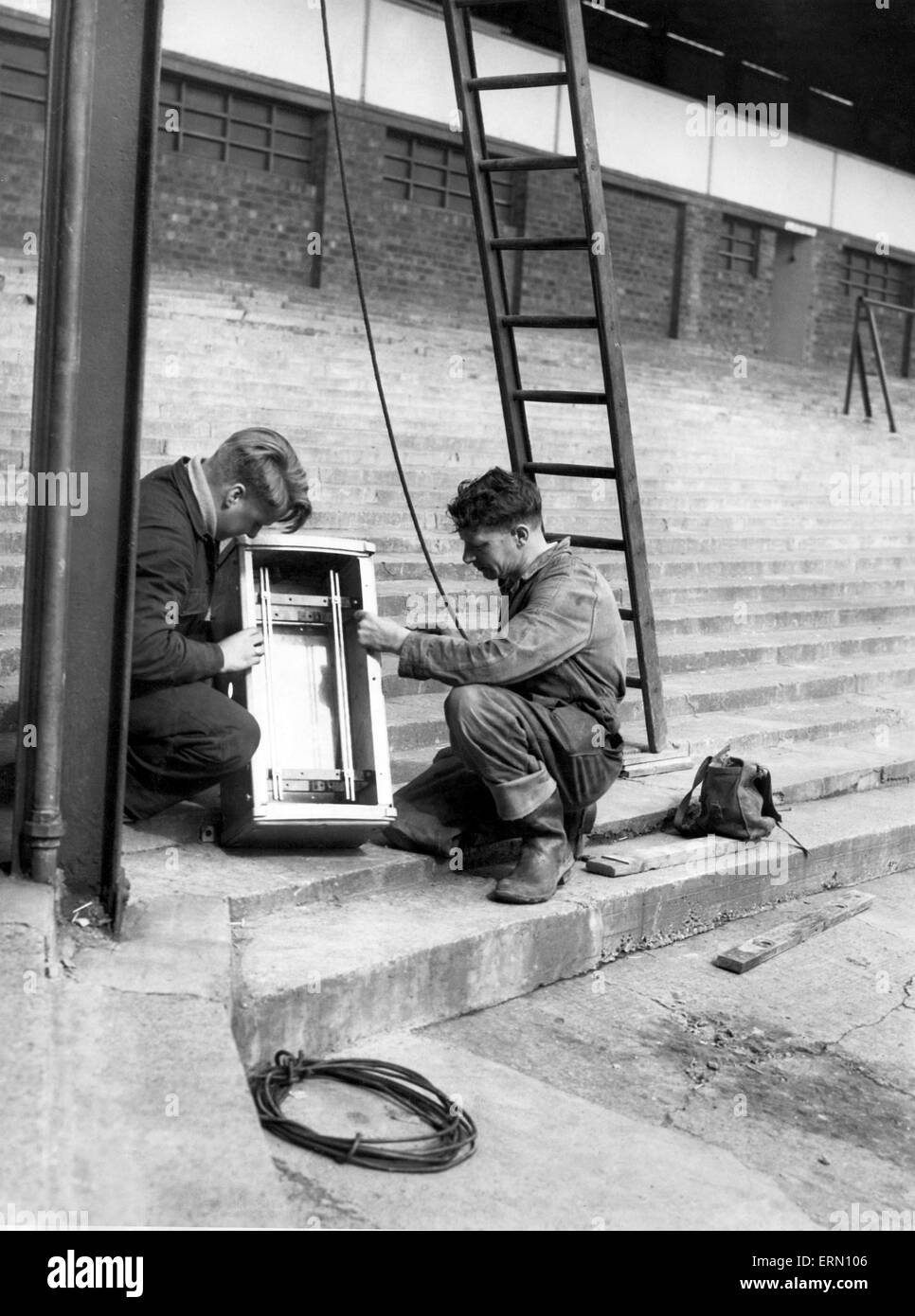 Mr C Urquhart and Mr A Moody working on a buzz bar chamber at the beginning of works on floodlights for St Andrew's, - Stock Image