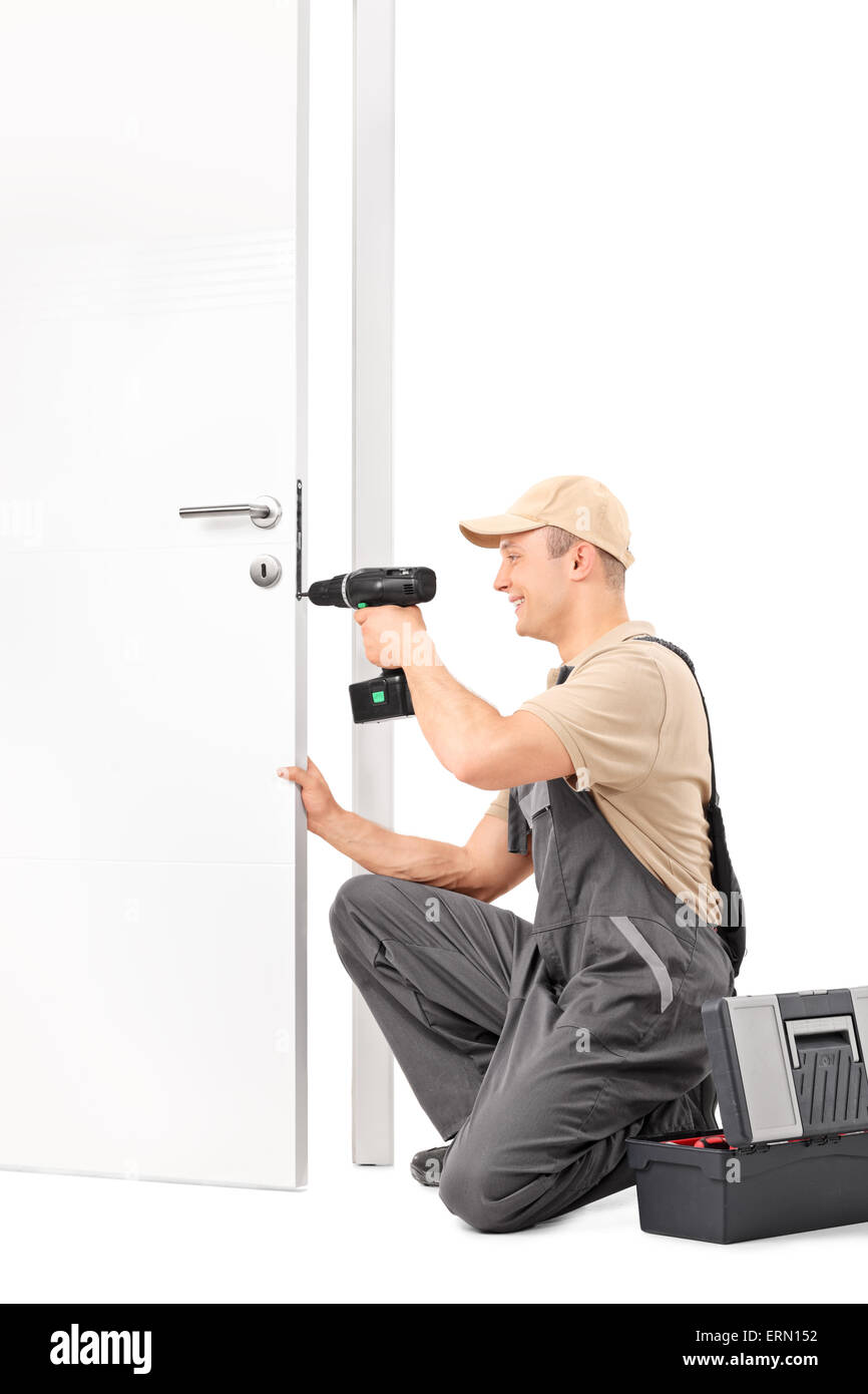 Vertical shot of a cheerful male locksmith installing a door lock with a hand drill isolated on white background - Stock Image